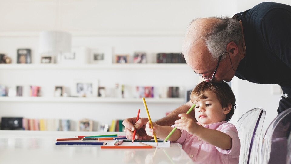 People indoor living room Grandfather help his grandson with drawing. Home, indoor, learning, people, improving people's lives.