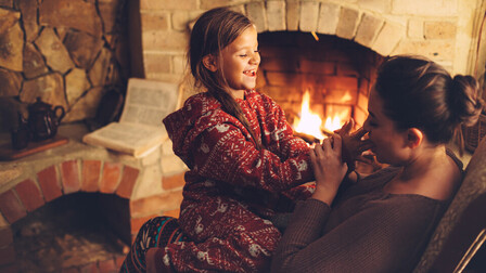 Mother and daughter in front of fireplace