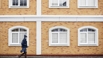 Young woman in a blue coat walking past a building of yellow brick.  Snowy weather in the city; Shutterstock ID 1058724476; Used for Sustainability Report 2018.