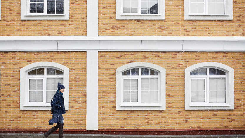 Young woman in a blue coat walking past a building of yellow brick.  Snowy weather in the city; Shutterstock ID 1058724476; Used for Sustainability Report 2018.   architecture; background; building; coat; exterior; facade; house; snow; stone; wall;